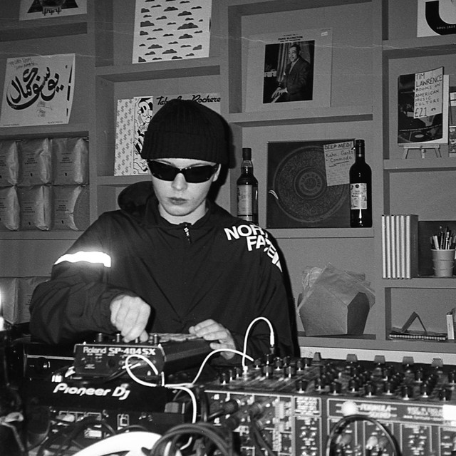 Black and white photo of Dylan in shades and a beanie, behind the mixer making music.