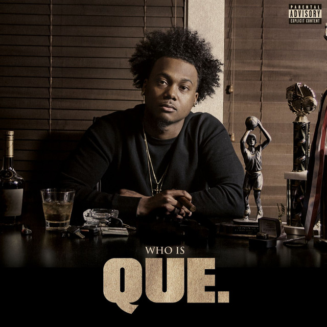 Who Is QUE.